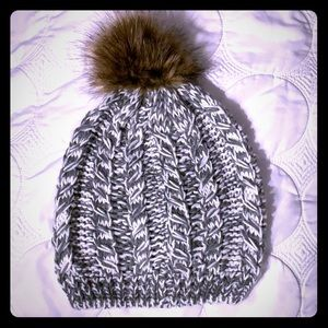 Gray and white beanie with brown faux-fur ball.